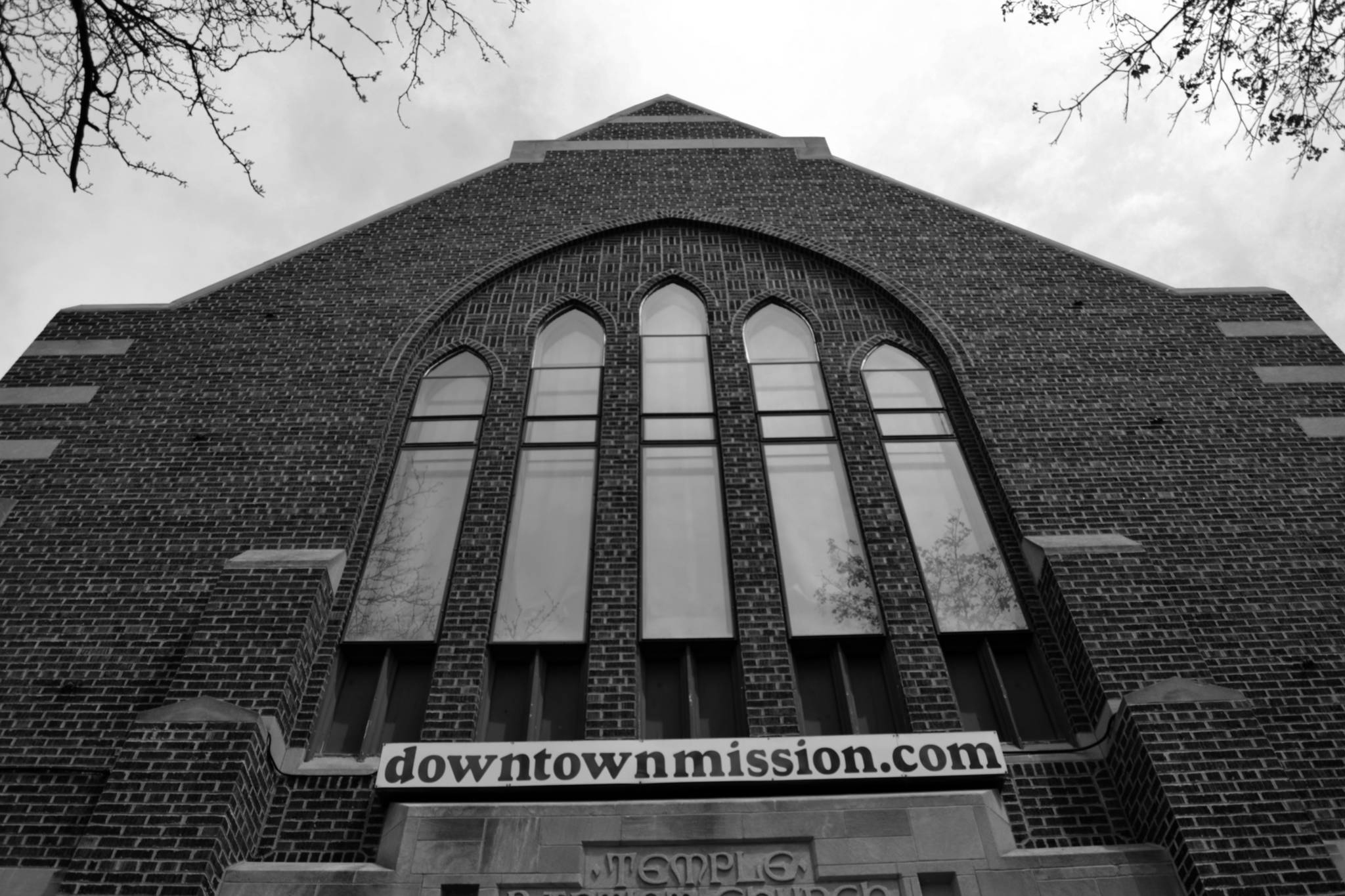 The front of the church of the downtown mission showing a banner displaying the website url.