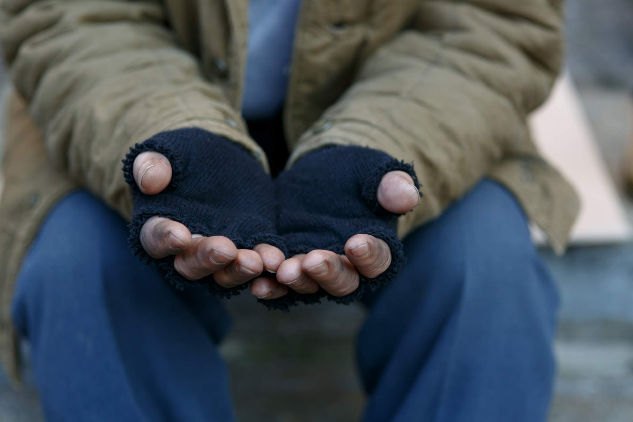 Homeless man holding hands out wearing torn, blue mitts.