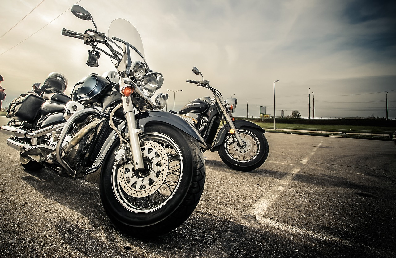 Two motorcycles parked in a parking lot.