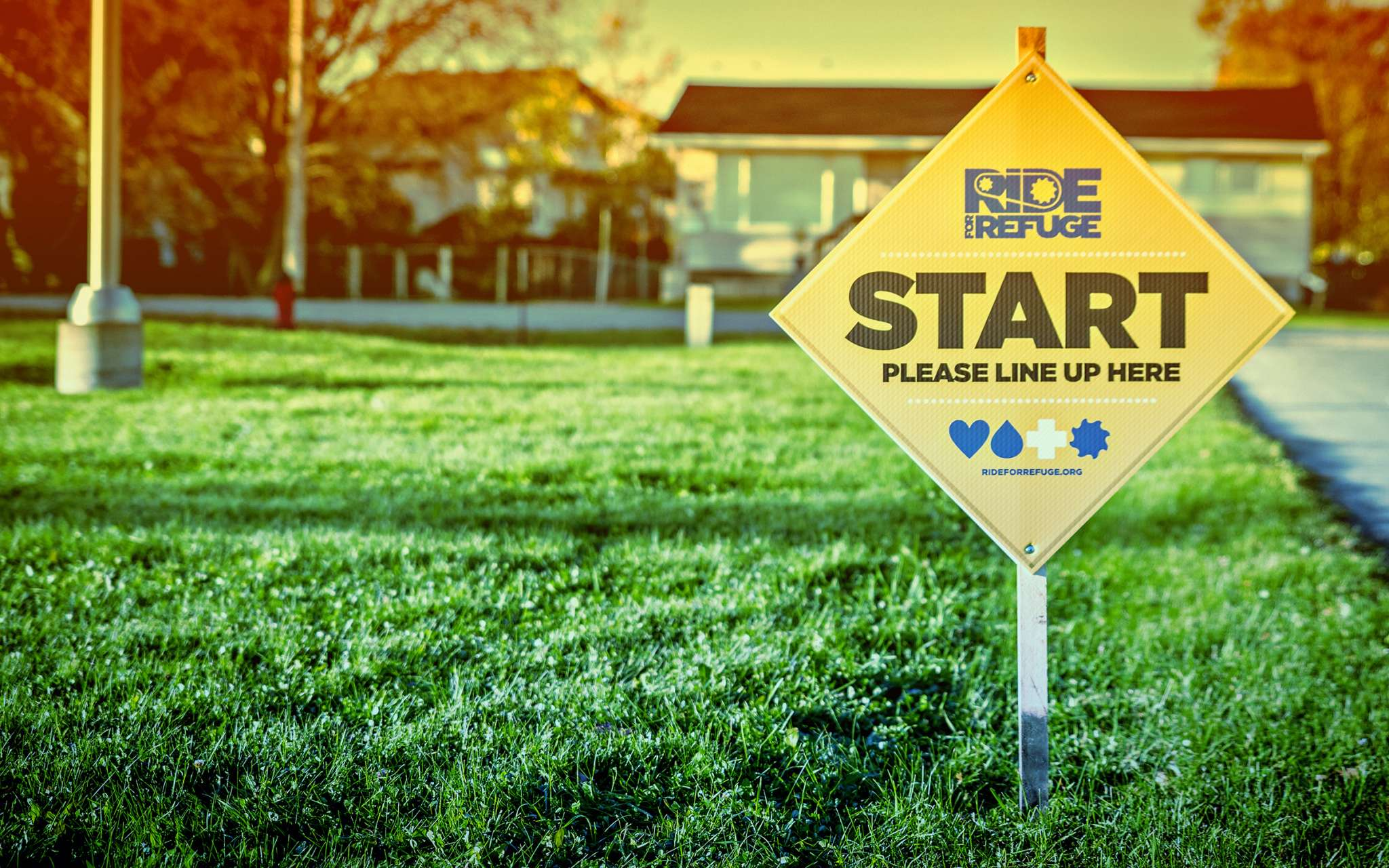 Start sign on lawn promoting the Ride For Refuge start line.